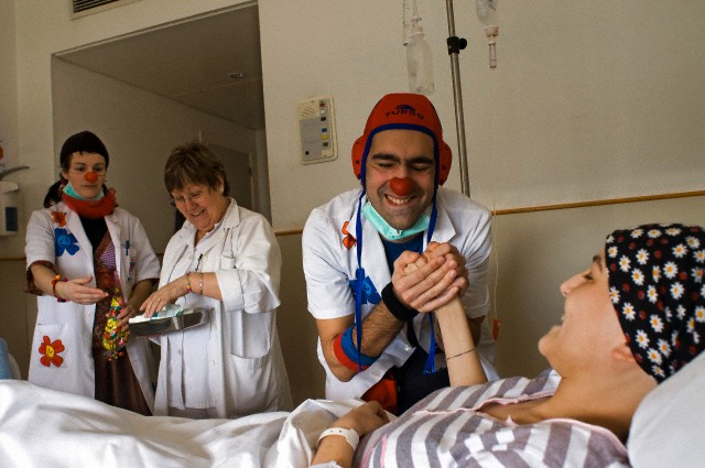 Hospital clowns joke with a cancer patient