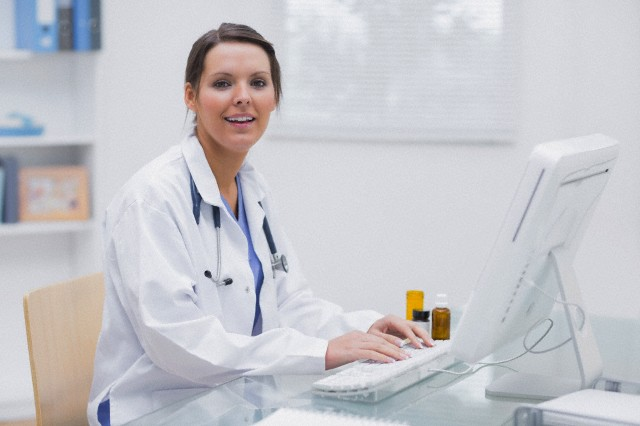 Portrait of female doctor using computer at clinic